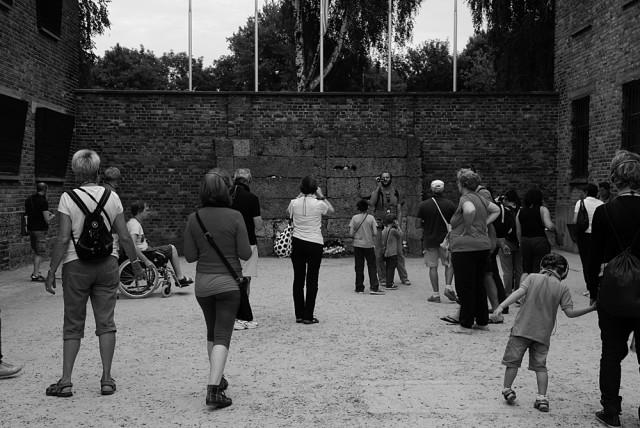 """Tutti sappiano e nessuno dimentichi Folla nel cortile recintato tra il blocco 10 e 11 che osserva il """"muro della morte"""". Il Blocco 11 ospitava il tribunale speciale e la prigione. Il cortile era luogo di fucilazioni, fustigazioni e torture"""